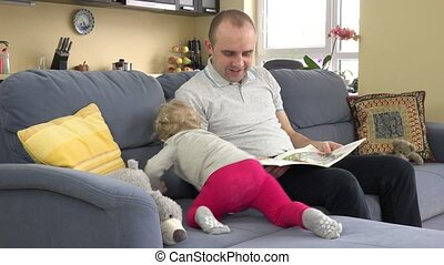 Cute toddler girl climb on sofa, sit near dad and read book...