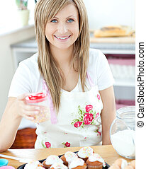 Attractive woman showing cakes in the kitchen at home