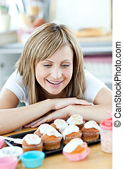 Cheerful woman looking at cakes in the kitchen