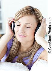 Portrait of a cheerful woman listening music in the kitchen...