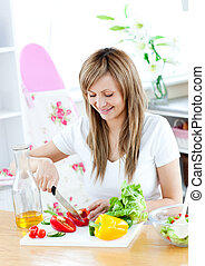 Cheerful woman preparing a healthy meal in the kitchen at...