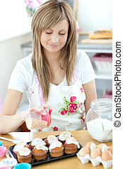 Teen woman preparing cakes in the kitchen at home