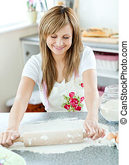 Teen woman preparing a cake in the kitchen at home