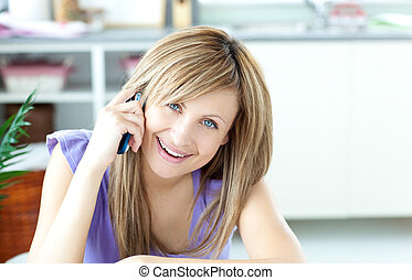 Delighted woman talking on the phone at home