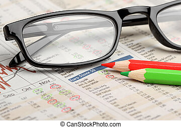 stock charts - glasses and red green pencils on newspaper...