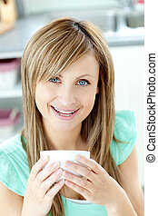 Delighted woman holding a cup of tea in the kitchen