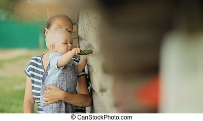 Beautiful baby boy sits at mum on hands and eat cucumber. Near an old wooden house