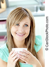 Self-assured woman holding a cup of coffee in the kitchen at...