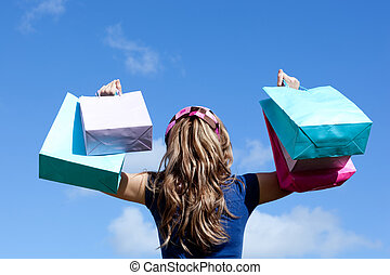 Young woman holding shopping bags outdoor against a blue sky...