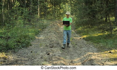 A man walks through the forest with a laptop and looking map He chooses the right direction