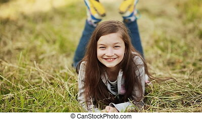 The young 11 year old girl lying on the grass. - Portrait Of...