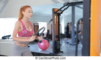 Woman pulling the rope of gym machine to her thighs at the...
