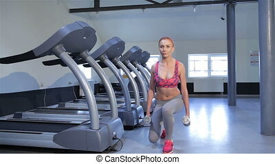 Woman does step-up exercise at the fitness centre -...