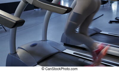 Woman listens the music on the treadmill at the fitness...