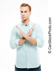 Young casual man showing stop gesture with arms crossed