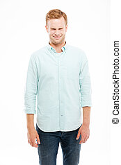 Smiling cute young man standing and squinting over white...