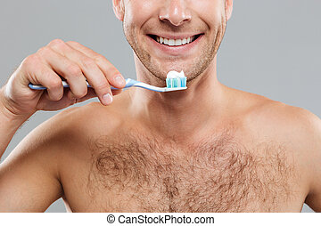 Closeup of cheerful young man holding toothbrush with toothpaste