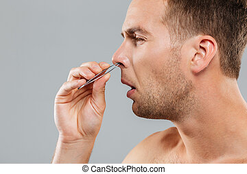 Side view of a man removing nose hair with tweezers isolated...
