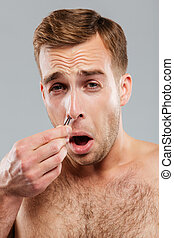 Close-up portrait of man removing nose hair with tweezers -...