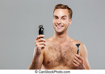 Young happy man what razor to choose isolated on the gray...