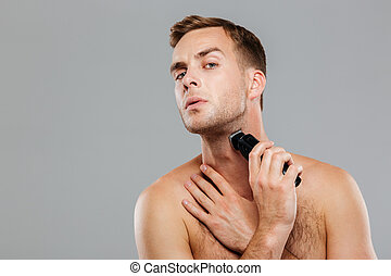 Young happy man shaving with electric razor