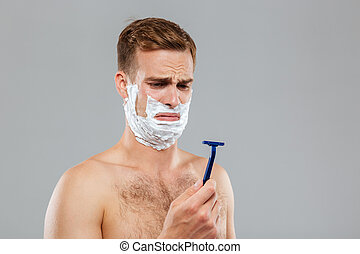 Portrait of a pensive man shaving