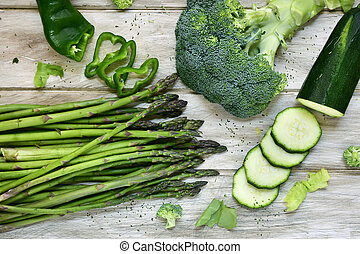 raw green vegetables on a rustic white table - high-angle...