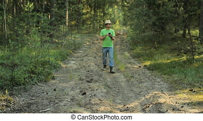 A man walks through the forest with the phone and looks at...