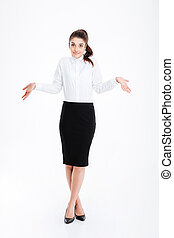 Portrait of a young businesswoman shrugging shoulders -...