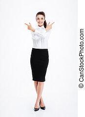 Cheerful young businesswoman standing and pointing away with...
