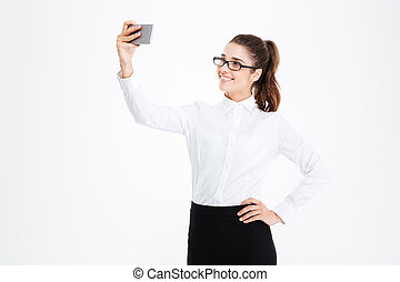 Smiling business woman in glasses making selfie using cell...