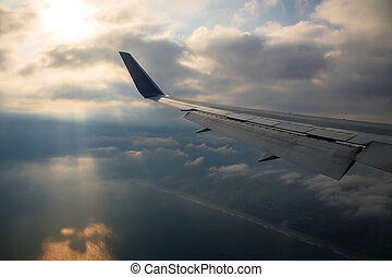 Airplane wing against ray light passing the cloud to sea