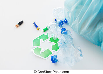 close up of used bottles and batteries recycling - waste...