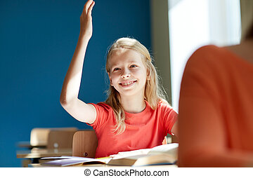 happy student girl raising hand at school lesson -...