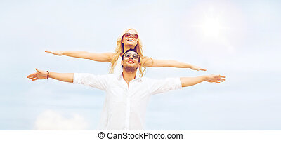couple holding hands up at sea side - summer holidays and...
