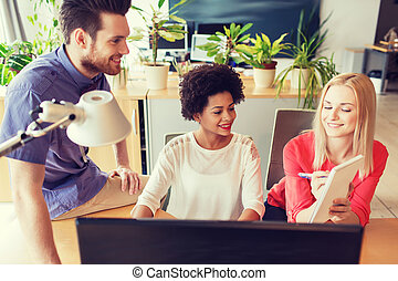 happy creative team with computer in office - business,...
