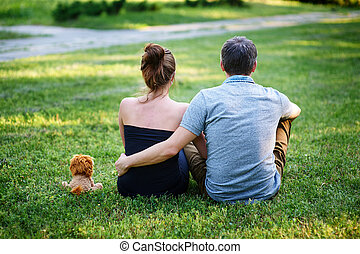 love couple sitting on the grass in summer park back