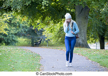 On the phone whilst walking - Young woman walking though a...