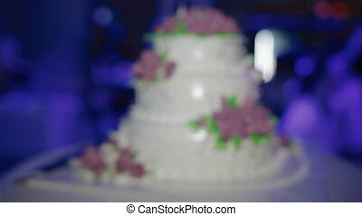 Beautiful wedding cake with purple roses in side light