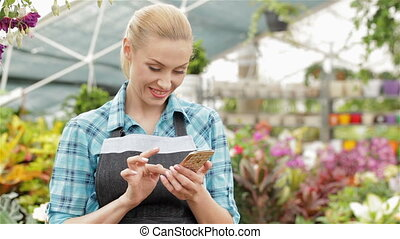 Female florist uses her smartphone at the garden centre -...
