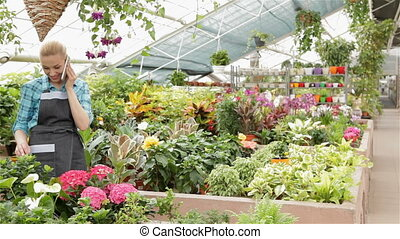 Female florist talking on the phone at the garden centre -...