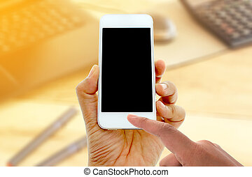 hand hold and touch screen smart phone on office desk with...