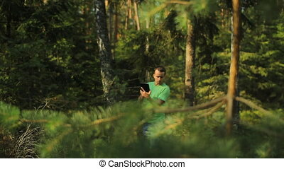 A man walks through the forest with a tablet PC and looking at the navigation application. He chooses the right direction