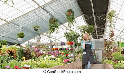 Female florist walks between flowerbeds at the garden centre...