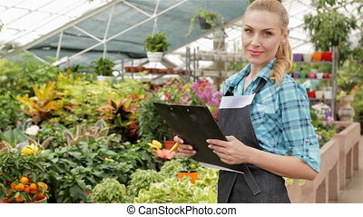 Female florist holds black tablet at the garden centre -...