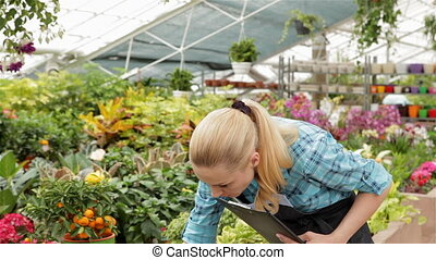 Female florist records data at the garden centre