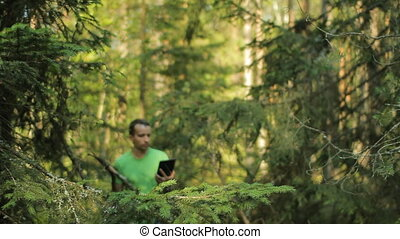 A man walks through the forest with a tablet PC and looking...