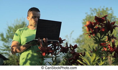 A man working at a laptop near beds of flowers early in the...
