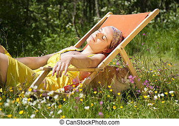 Vacation! - Woman relaxing in a deck chair i the sunlight. A...