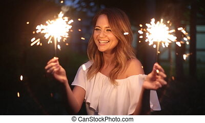 happy young woman with sparklers - smiling young woman...